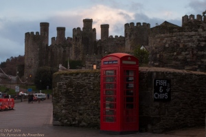 Fish and chips sign and red phone box with Conwy Castle in the background